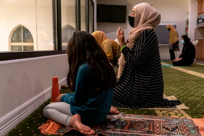 Anjum Hanafi prays with her daughter Aiya Chawdhry, 8, as they observe Ramadan at the Islamic Center of Lake Travis on Monday.
