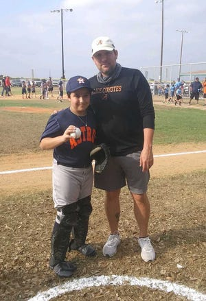Coach Kyle Atwood stands with Astro catcher Manny Ramos at the opening day ceremonies.