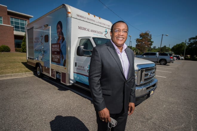 Medical Associates Plus CEO J.R. Richards stands with the health center's COVID-19 van. He said staff were calling patients Tuesday who had been set to receive the Johnson & Johnson vaccine to cancel and potentially reschedule them to receive the Moderna vaccine.
