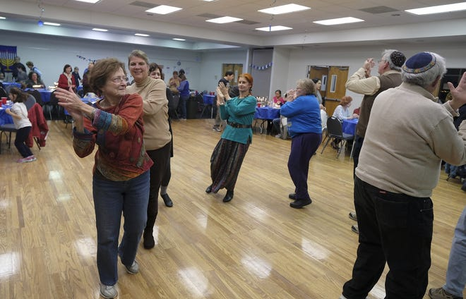 Jackie Cohen, left, leads a group of dancers in a traditional Israeli dance during the 2018 Community Hanukkah Latke Dinner at the Augusta Jewish Community Center in Evans.