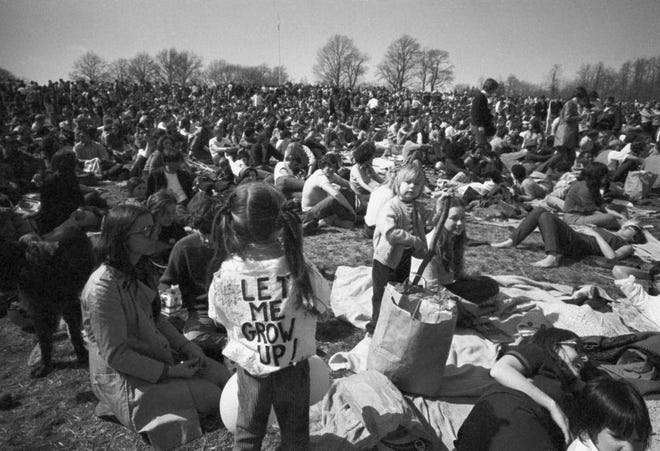 """A crowd of more than 20,000 observing the first Earth Day at Philadelphia's Fairmount Park includes a little girl wearing a """"Let me grow up!"""" T-shirt."""