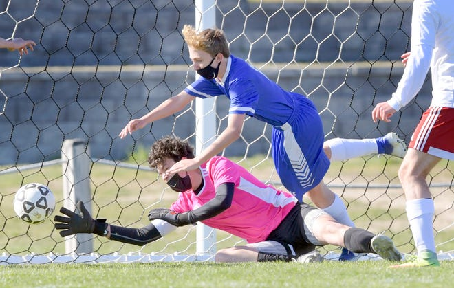 Anthony Munroe of Upper Cape scores one of his two goals as Bishop Connolly goalie Liam Marshall reaches to try to make the stop in Tuesday's game.