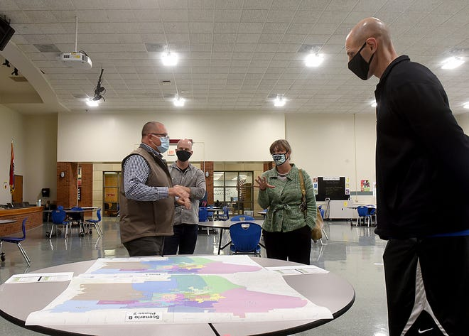 Randy Gooch, left, chief operating officer at Columbia Public Schools, listens as Jessica Leonard, center, asks questions about one of the district's possible boundary scenarios April 13 during a feedback session at Gentry Middle School.