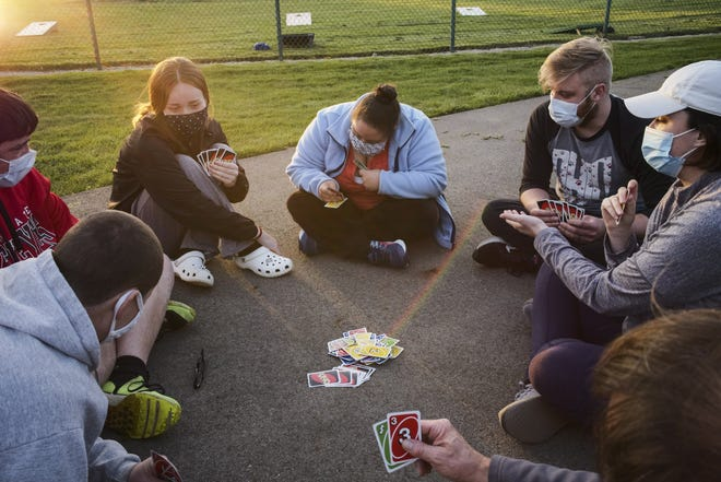 Franklin County Special Olympics volunteers and athletes play a round of Uno during a new social club in early April at John F. Kennedy Park in Reynoldsburg. The organization is offering spring athletes a chance to visit with friends and coaches on their off-practice night.