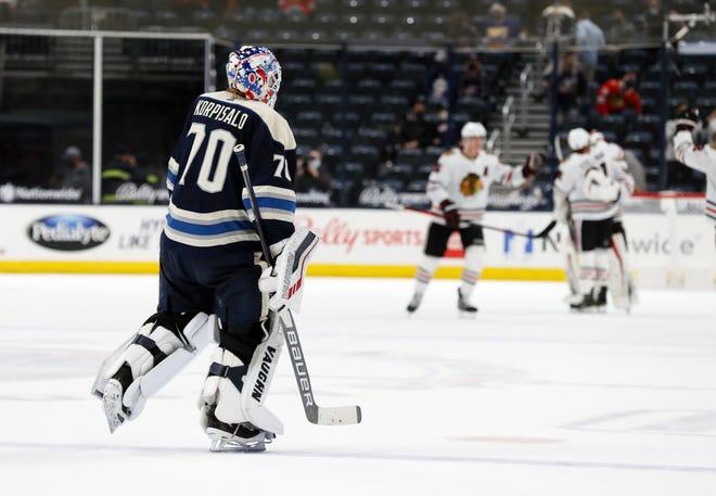 Blue Jackets goaltender Joonas Korpisalo skates off the ice while the Blackhawks celebrate their overtime win on Monday. Chicago went6-2-0against Columbus this season.