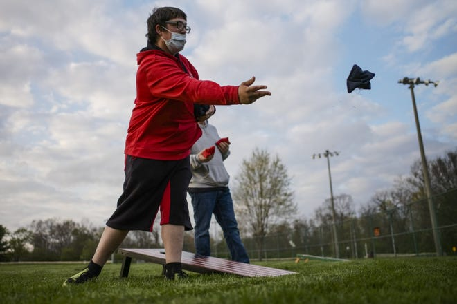Franklin County Special Olympics athlete Ryan Lowrey plays a game of bags with a coach during the group's social club on Monday, Apr. 12, 2021 at John F. Kennedy Park in Reynoldsburg, Ohio. The organization decided to offer a social club component for spring athletes who can come to the practice venue on their off-practice night and visit with friends and coaches.