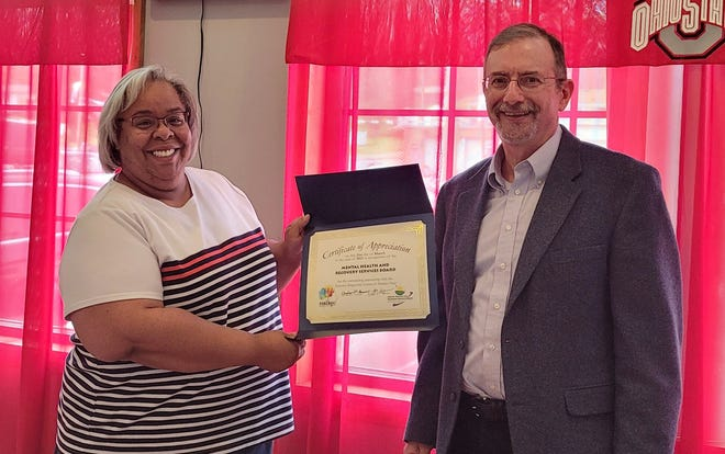 Misty Cromwell, executive director of the Mental Health & Recovery Services Board, presents a certificate of appreciation to Dr. Andrew Reisner, executive director of the Forensic Diagnostic Center of District Nine.