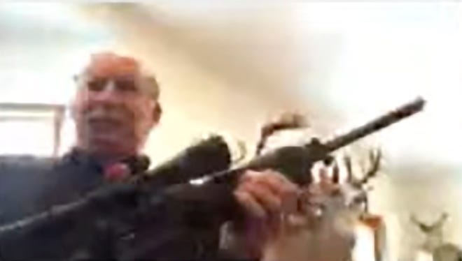 In this screen grab taken from a Zoom meeting provided by the Grand Traverse County Board of Commissioners, Grand Traverse County Commissioner Ron Clous holds a rifle at his home during a county commissioner meeting Wednesday, Jan. 20, 2021, in Michigan. Clous displayed the rifle during the online meeting in response to a citizen's comments about a far-right extremist group, drawing backlash from some local residents.