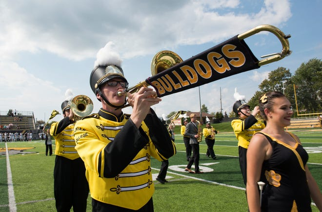 Adrian College Marching Band member Blayk Olson (with Bulldogs-themed trombone) is pictured performing in 2019 at Docking Stadium.