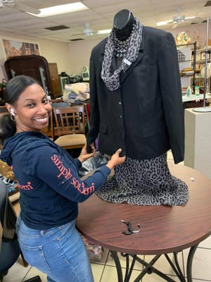 Katrina Billie, one of several Billie family members who have opened Billie's Tip Top Shop in Thomasville, dresses a mannequin in the new store on West Main Street in Thomasville.