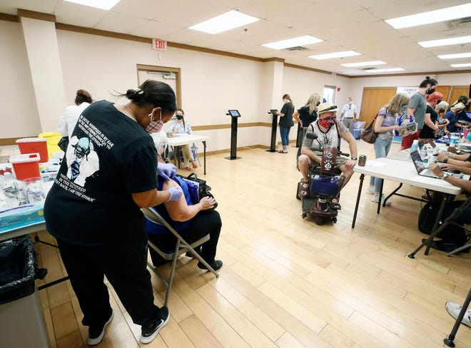 A healthcare worker administers a dose of Moderna's COVID-19 vaccine at a clinic at Wes Crile Park in Deltona where appointments weren't needed Tuesday, April 13, 2021. The clinic was put on by Family Health Source.