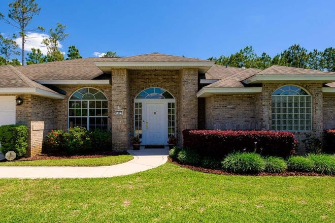 The brick exterior shows the solid construction of this Ormond Beach home, which is surrounded by beautiful landscaping and backs up to a preserve.