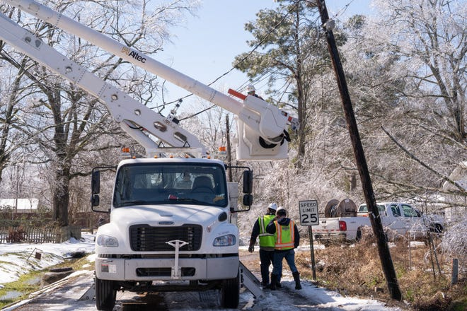 Crews work on power lines during the winter weather in February.