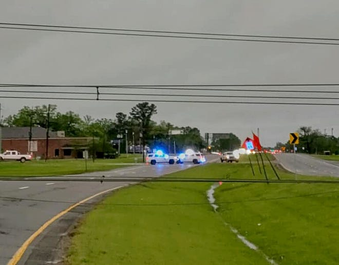 Louisiana State Police Troopers work along Airline Highway early April 10. Both directions were closed due to downed power lines. Traffic was diverted to Old Perkins Road and Highland Road in East Baton Rouge Parish.