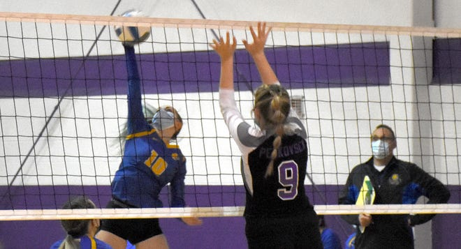 Mt. Markham's Chelsea Osborn hits the ball with Little Falls Mountie Claire Petkovsek (9) setting up a block attempt Monday.