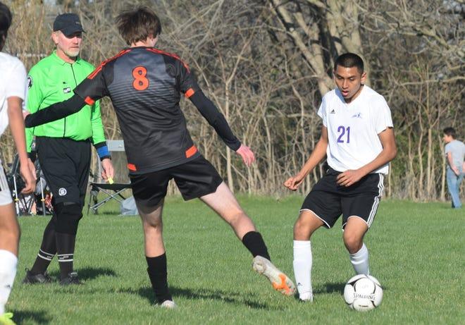 Burlington's Parker Beardsley (21) and Washington's Zac Stout battle for the ball during a Southeast Cionference boys soccer match Monday at Washington. The Demons won, 5-1.