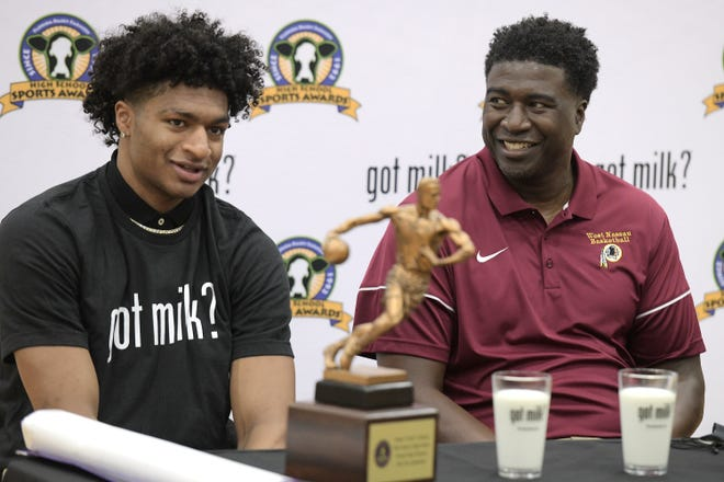 Deebo Coleman receives the Florida Dairy Farmers Mr. Basketball award during an April 13 ceremony as his father and coach Ran Coleman, right, looks on.
