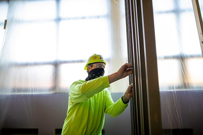 A worker assembles a frame in a second-floor hallway at Galesburg High School on Tuesday, April 13, 2021.