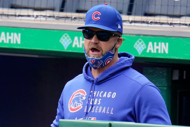 Chicago Cubs manager David Ross stands in the dugout during a game against the Pittsburgh Pirates in Pittsburgh, Sunday, April 11, 2021.