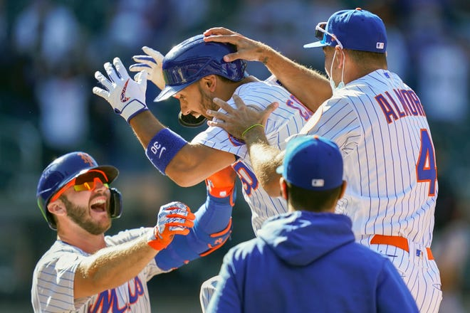 New York Mets' Michael Conforto (30) celebrates after being hit by a pitch and scoring the winning run on loaded bases during the ninth inning of a game against the Miami Marlins on Thursday, April 8, 2021, in New York.