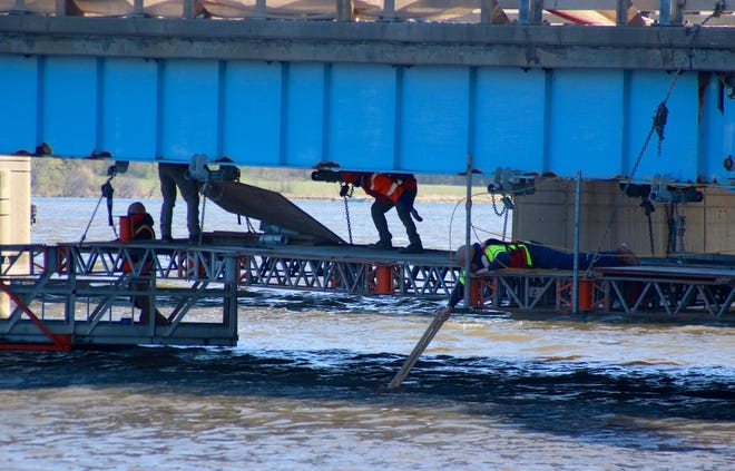 Construction crews work Tuesday, April 13, 2021, underneath the I-196 bridge over the Kalamazoo River near Schultz Park in Douglas, Mich. The Michigan Senate has passed a plan to use $1.6 billion in federal funding to repair locally owned bridges in the state.