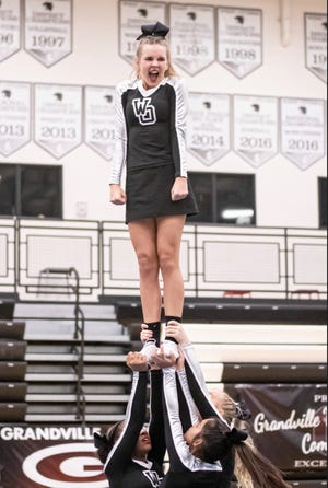 West Ottawa's Abby Walton being lifted by her teammates during a cheer competition