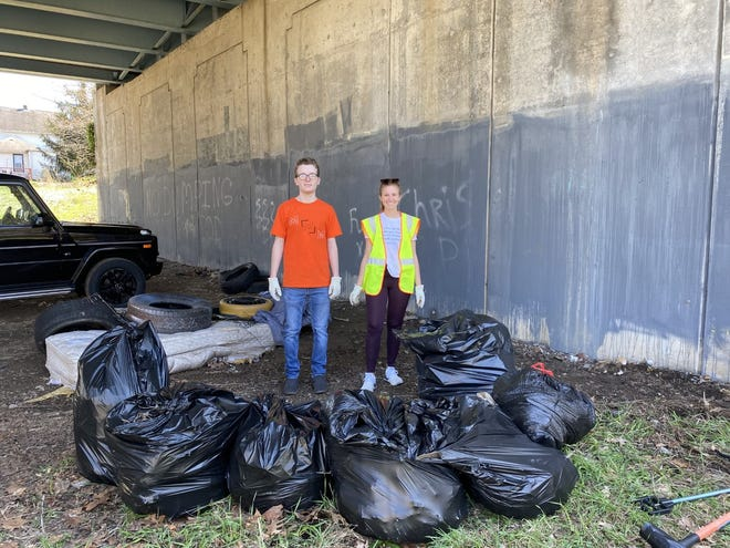 Christian Lamb and Alexis Brittany, members of Manners Matter in Massillon, are shown with a number of garbage bags, tires and other debris collected during a cleanup under the Tremont Viaduct last spring. On May 1, the group will focus their efforts on Reservoir Park.