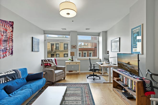 The living-dining room is flooded with light from its rooftop view of classic North End buildings.