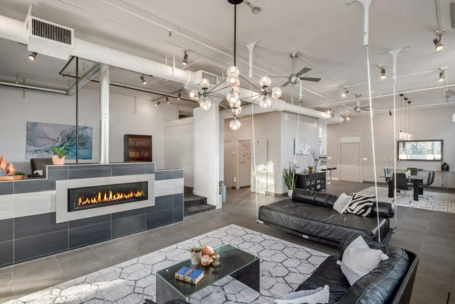 Illuminated by light pouring through oversized windows, the living area features a suspended sofa and a gas fireplace with custom tile on the surround.