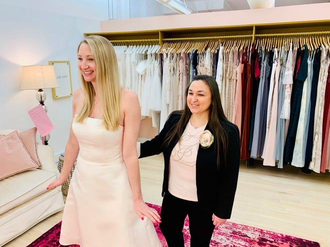 At the Gilded Social, a bridal shop in Columbus, Ohio, owner Tanya Rutner Hartman helps customer Cristin Lee try on a gown at the shop on April 2, 2021. Although weddings and other big celebrations are going back on the calendar in the United States, business owners who make those events happen expect a slow recovery from the impact of COVID-19. Hartman sees a shift in how couples feel about weddings, a change that can affect other businesses in the events industry as well. [Gilded Social via AP]