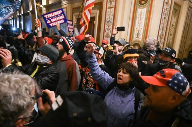 Sue Ianni, shown in a published photo raising her right arm in defiance inside the U.S. Capitol on Jan. 6, is not named in a resolution to be introduced at Town Meeting that condemns the attack.