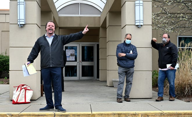 Auctioneer Paul Zekos, left, auctions off the former Aegean Restaurant at 257 Cochituate Road (Rte. 30) in Framingham on Tuesday. At right is the winning bidder, Paul Linder of Brookline, who bought the property for $1.1 million. Linder was married at the restaurant in 2010. At center is developer Emad Benyamin, who offered the second-highest bid.
