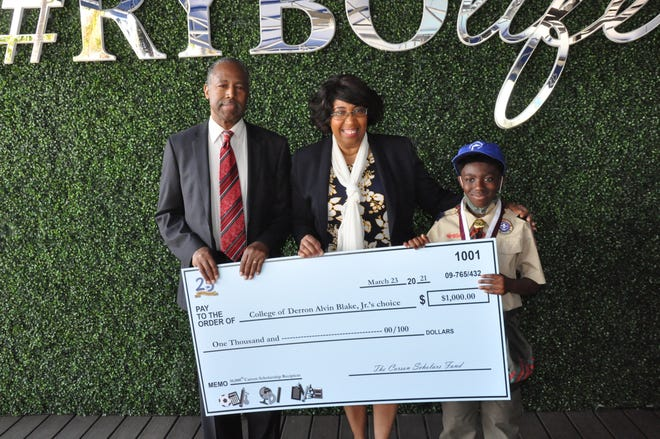 Derron Blake Jr, right, poses with Dr. Ben and Candy Carson and his $1,000 scholarship check -- the 10,000th given by the Ben Carson Foundation.
