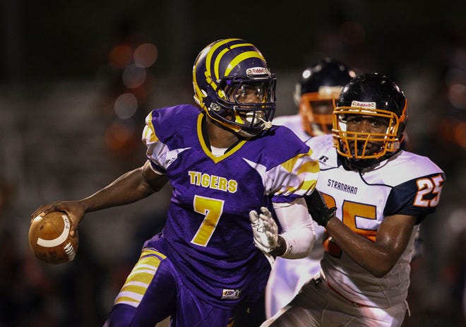 Boynton Beach quarterback Lamar Jackson scrambles while being pursued by Ft. Lauderdale Stranahan's Cleveland Singletary during a game Friday, September 26, 2014. Jackson signed with ACC's Louisville, but this past year, just one player from Palm Beach County signed with a school in a Power 5 conference.