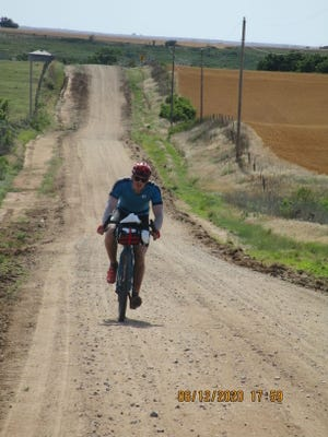 A road race competitor from 2019 rides across pastureland in Pratt or Barber county, part of the Open Range Gravel Race course.