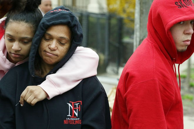 Ybelka Pena, mother of Isaias Bulus, who was shot and killed early Monday, is consoled by her daughter Leonies Taveras, 14, while visiting the shrine to him on Atlantic Avenue. At right is family friend Kelvin Somoza.
