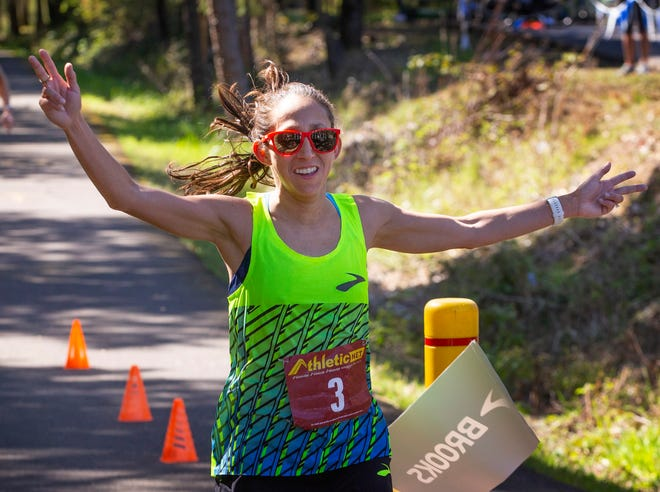 Des Linden crosses the finish line of a 50K in under three hours to break the international record for the distance on a COVID-19 friendly course laid out along Dorena Lake near Cottage Grove.