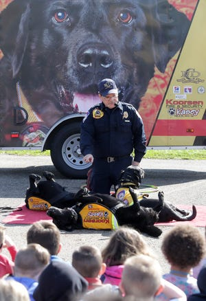 Firefighter Jeff Owens, a Carmel, Indiana, uses his black Labradors Kasey, Kali and Karmel to demonstrate the stop, drop and roll technique for students at Gorrell Elementary School on Tuesday. The group travels across the country teaching kids of all ages fire and life safety skills.