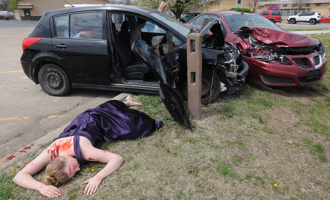 Sacred Heart S.A.F.E., Seatbelts Are For Everyone, club member Teghan Slagle, 18, pretends to be dead during the prom DUI mock accident in the Sacred Heart Jr.-Sr. parking lot on Monday.