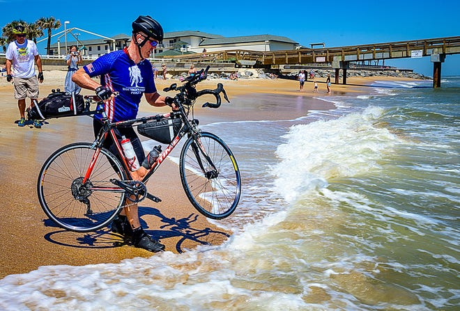 Retired U.S. Army Col. Dave Parramore dips his bicycle in the Atlantic off St. Augustine Beach on Tuesday to celebrate his crossing the county on the bike to raise money for the Wounded Warrior Project. Parramore left San Diego on March 1 and raised about $30,000 for the organization.