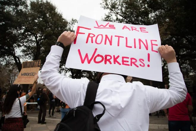 Protesters hold signs advocating for the protection of frontline workers at the Texas Capitol, in Austin, in March in response to Gov. Greg Abbott ending the statewide mask mandate. Texas lawmakers were considering legislation that would, among other things, prevent cities from requiring businesses to provide paid sick leave to employees.