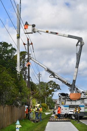 Florida Power & Light employees install an 8,000-pound concrete power pole on a main power line along De Soto Road near Mink Road in Sarasota in this May 2019 file photo. The work was part of a larger project FPL is undertaking to harden the power grid across the state.
