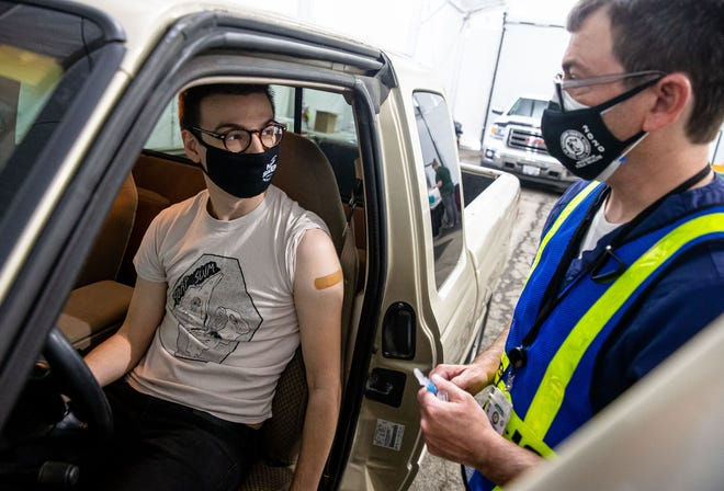 """Mitch Baker, 26, receives his first dose of the Moderna COVID-19 vaccine from Mike Butler, a registered nurse with the Sangamon County Dept. of Public Health in the COVID-19 vaccine drive-thru at the public health department in Springfield Tuesday. """"For one I'm ready to get back to normal,"""" said Baker, who signed up for an appointment immediately after hearing that anyone over 16 in Illinois was eligible for the vaccine. """"But also it's a group effort and it's one of those things that if everybody does their part and gets their vaccine hopefully other people can stay safe as well."""""""