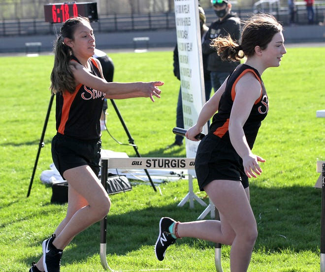 Naideline Luna-Bucio hands off the baton to Annabelle Pant in the 3,200-meter relay for Sturgis on Tuesday.