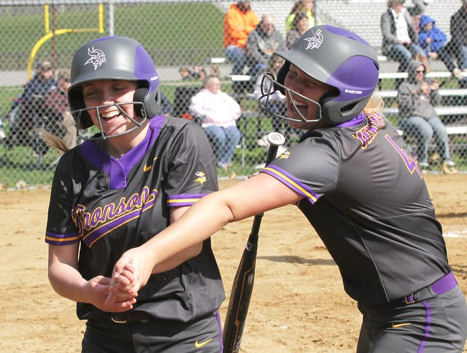 Bronson's Jaydn Cary and Lynsey Smith share a smile and a laugh after Cary scored a run in the first game on Monday afternoon.