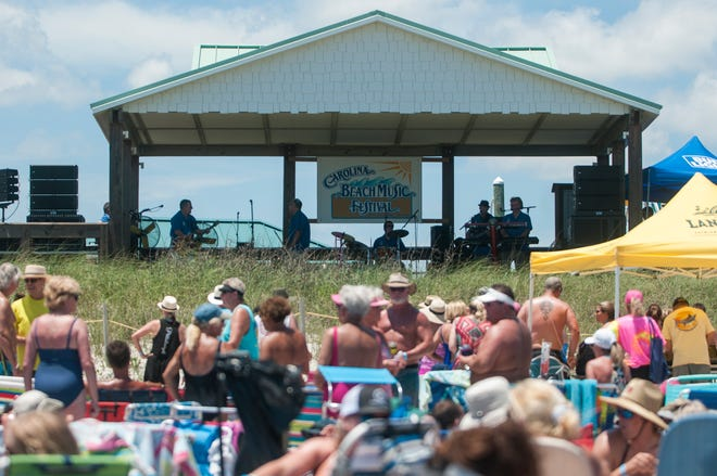 People listen to music on the beach and in the water at the Carolina Beach Music Festival at Carolina Beach on Saturday, June 2, 2018.
