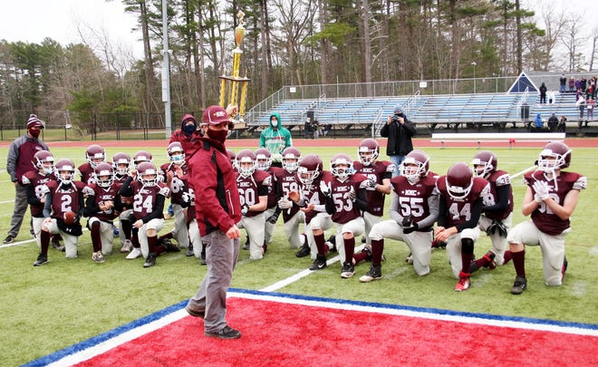 Mitchell Memorial Club Football 8th Grade Team head coach Bob Mosley raises the championship trophy in celebration of Sunday's win over Abington in the OCYFL Super Bowl. The Cougars won by a 28-0 final.