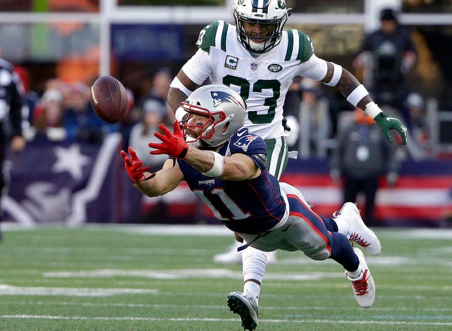 New England Patriots wide receiver Julian Edelman stretches out for a pass in front of New York Jets safety Jamal Adams in Foxborough, Mass.