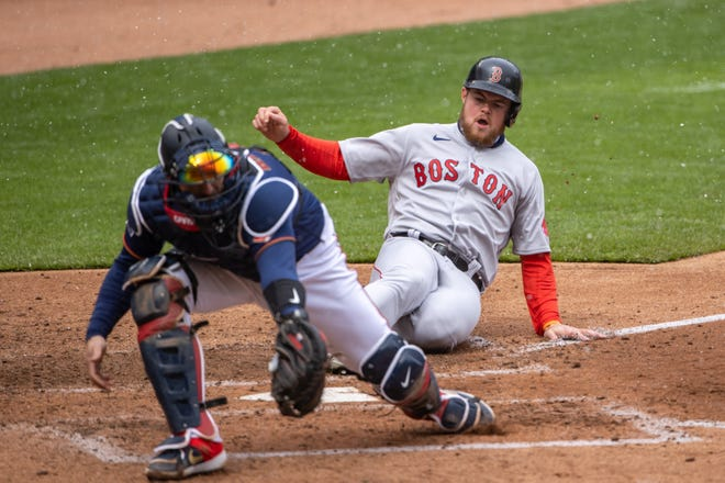 Red Sox second baseman Christian Arroyo  slides safely into home before Twins catcher Mitch Garver can catch the ball and make a tag in the fifth inning Tuesday in Minnesota.