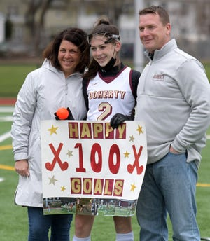Doherty's Elle Murray celebrates her 100th career goal with her parents at Foley Stadium after Monday's game.